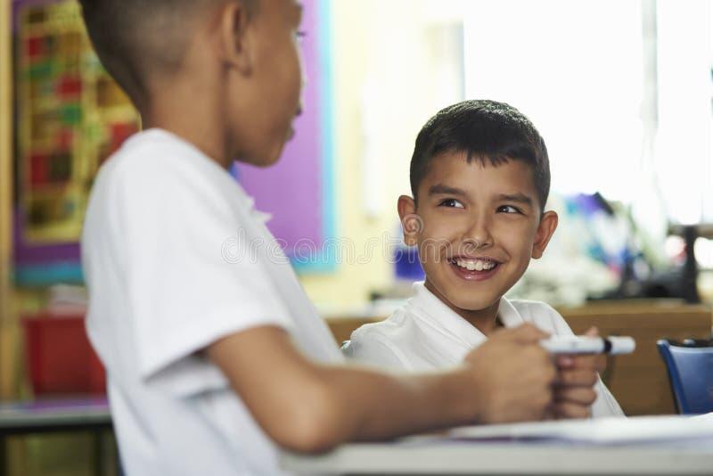 Stäng sig upp av två grundskola för barn mellan 5 och 11 årpojkar som påverkar varandra i grupp royaltyfria bilder