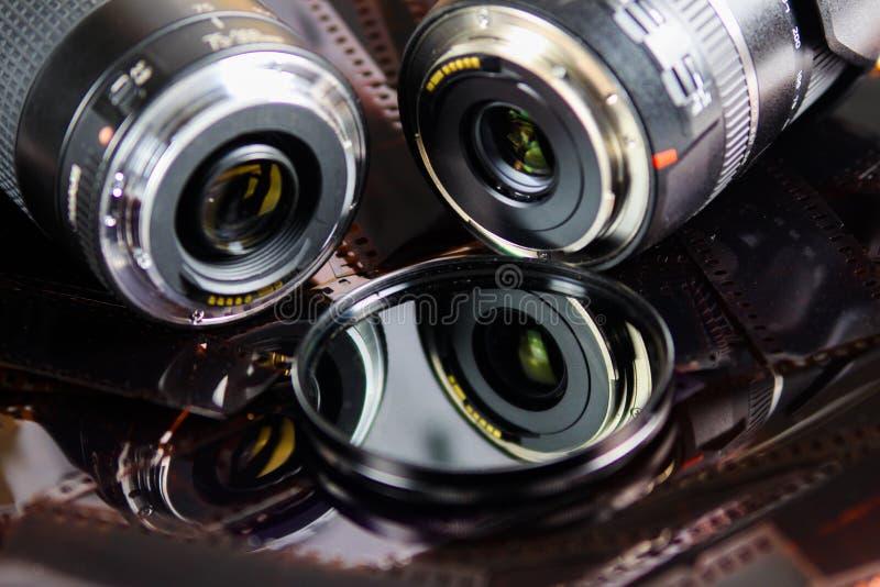 Stäng sig upp av två kameralinser med det isolerade runda filtret på remsor för negativ film royaltyfria foton