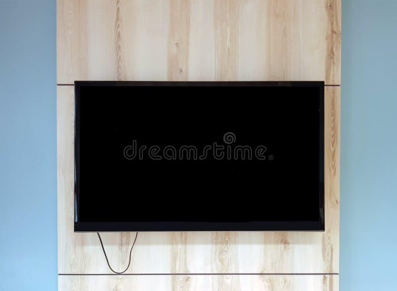 Stäng sig upp av TVuppsättning på träväggen som i regeringsställning hänger ovanför bänk royaltyfri foto