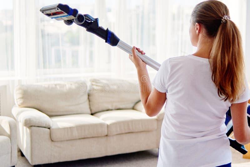 Stäng sig upp av ung kvinna i den vita skjortan som rymmer i trådlös dammsugare för händer, medan göra ren i vardagsrum hemma, ti royaltyfri bild