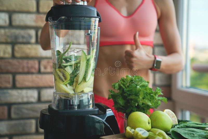 Stäng sig upp av ung kvinna med blandaren och göra grön grönsaker som gör detoxen för att skaka eller den hemmastadda smoothien royaltyfria foton