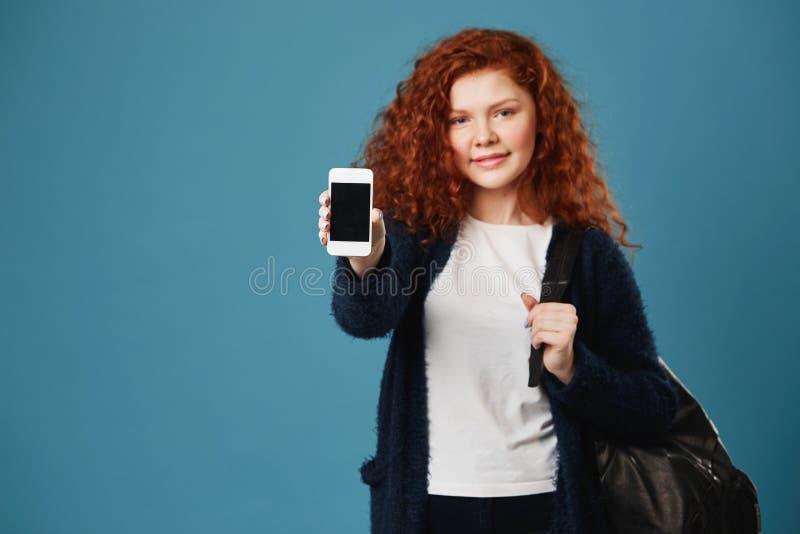Stäng sig upp av ung ljust rödbrun studentflicka med krabbt hår och fräknar som bär den vita t-skjortan och, svärta koftavisninge arkivbilder