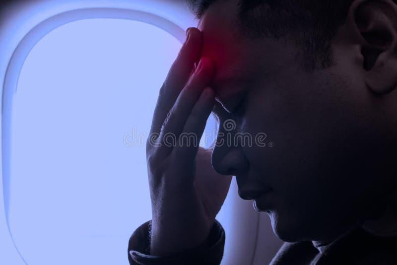 Stäng sig upp av ung man med huvudvärk och att trycka på hans panna med handen royaltyfria foton