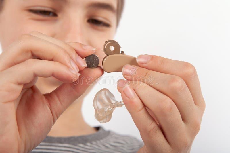Stäng sig upp av unga en pojkes händer som byter ut ett batteri av en hörapparat med det öppna smetrummet royaltyfri bild