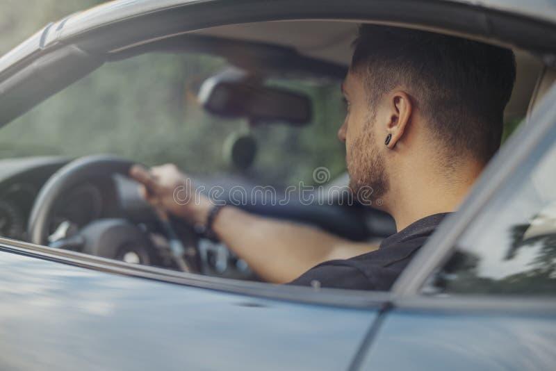 Stäng sig upp av ungt attraktivt mansammanträde i den svarta bilen royaltyfri foto