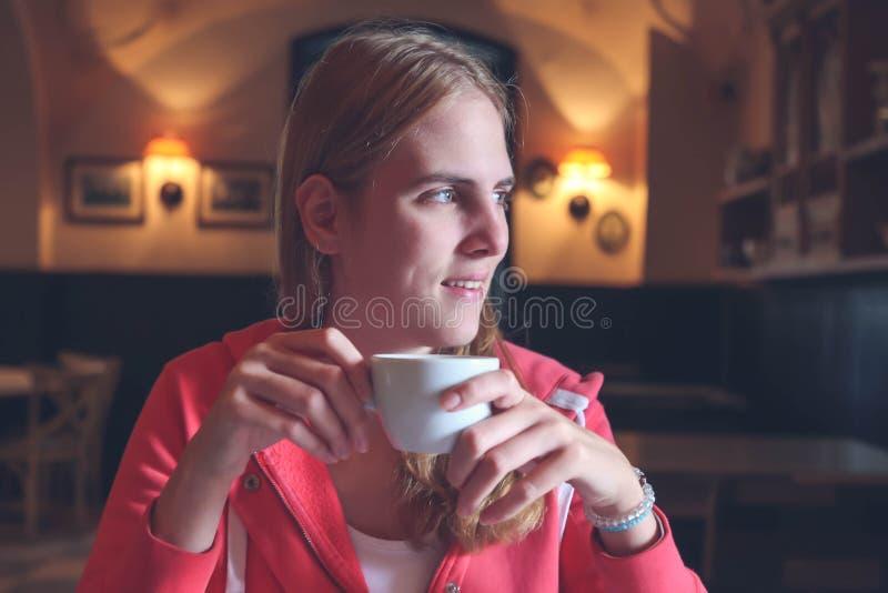 Stäng sig upp av ungt härligt flickasammanträde i ett kafé som tänker och royaltyfri bild