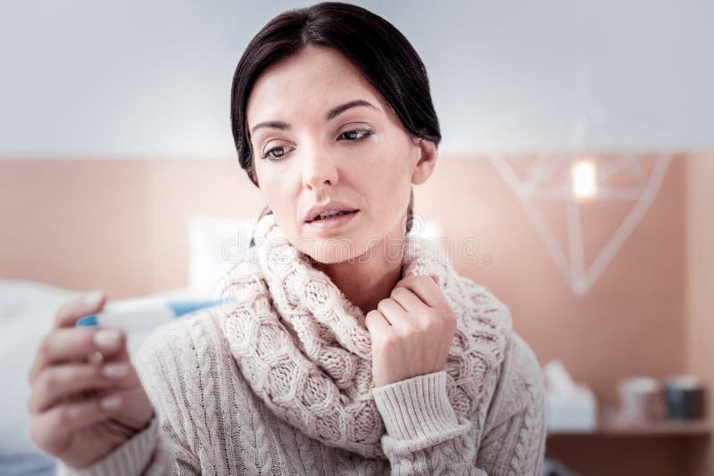 Stäng sig upp av uppriven kvinna med termometern arkivbilder