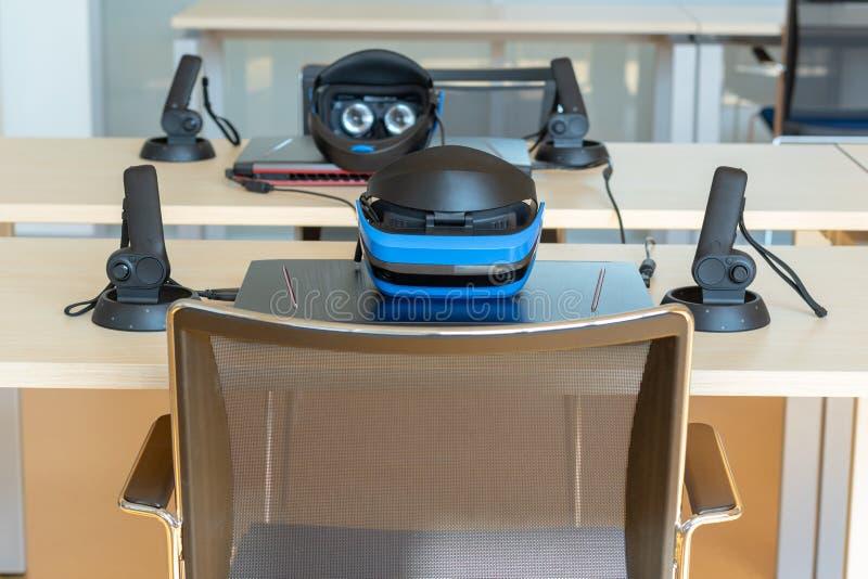 Stäng sig upp av uppsättningar för virtuell verklighet en VR i ett klassrum - hörlurar med mikrofon, kontrollant och dator royaltyfria bilder