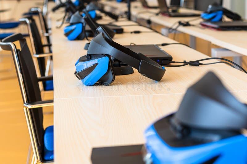 Stäng sig upp av uppsättningar för virtuell verklighet en VR i ett klassrum - hörlurar med mikrofon, kontrollant och dator royaltyfri fotografi