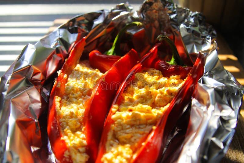 Stäng sig upp av välfyllda röda paprikaspanska peppar med fårfetaost som kryddas med den kryddiga chili som grillas i aluminiumfo royaltyfria bilder