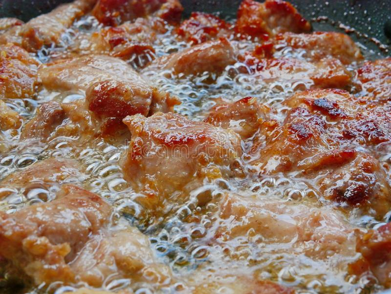 Stäng sig upp av välkokt djupt steka griskött, i att koka/som hemma bubblar matolja en stekpanna - kock arkivfoton