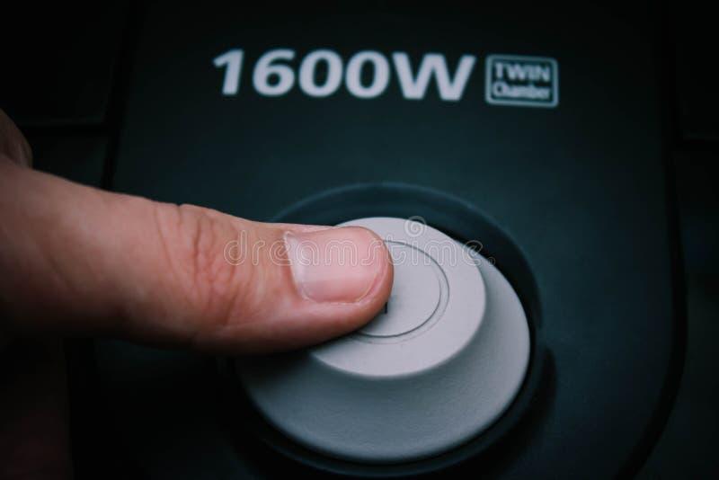 Stäng sig upp av vänder på knappen av dammsugare på golv av vardagsrum royaltyfri foto