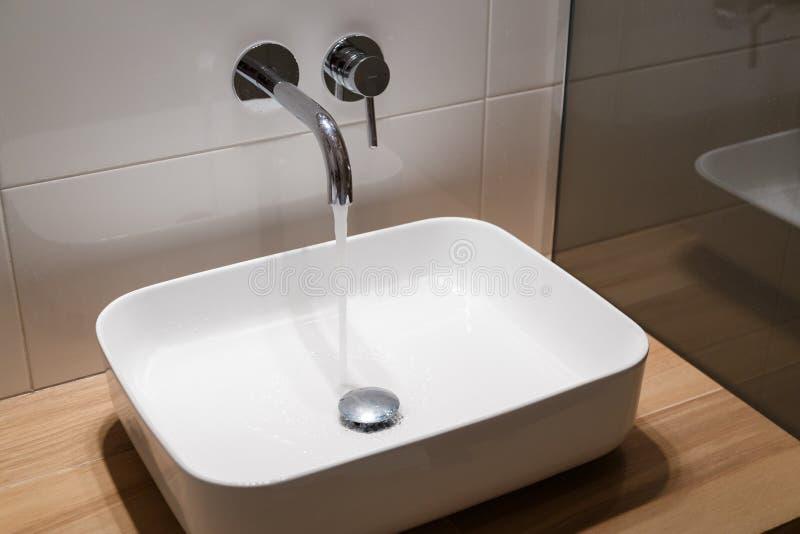 Stäng sig upp av vask och vattenkranen på trähylla i den vita badruminre arkivbilder