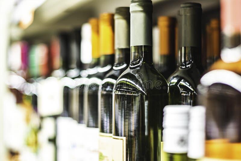 Stäng sig upp av vinflaskor på hylla i lager royaltyfri bild