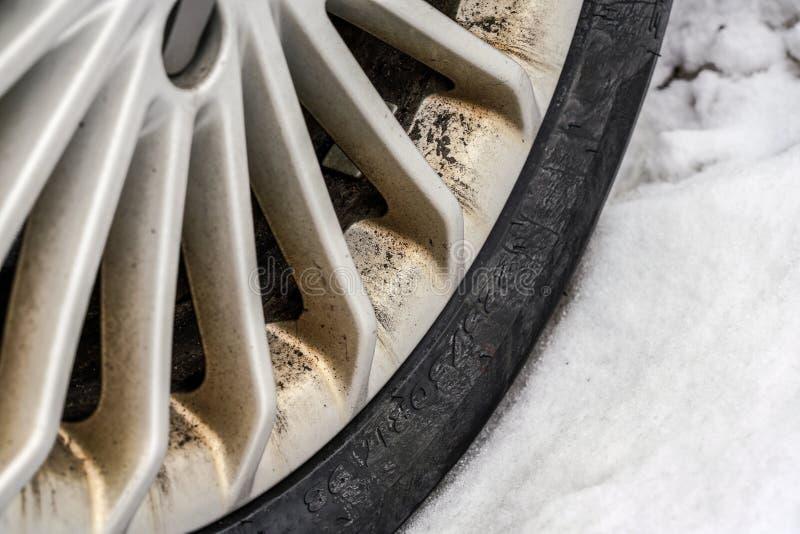 Stäng sig upp av vintergummihjulet, aluminiumbilkant, smutsa ner från damm och olja, snö bredvid den royaltyfri bild