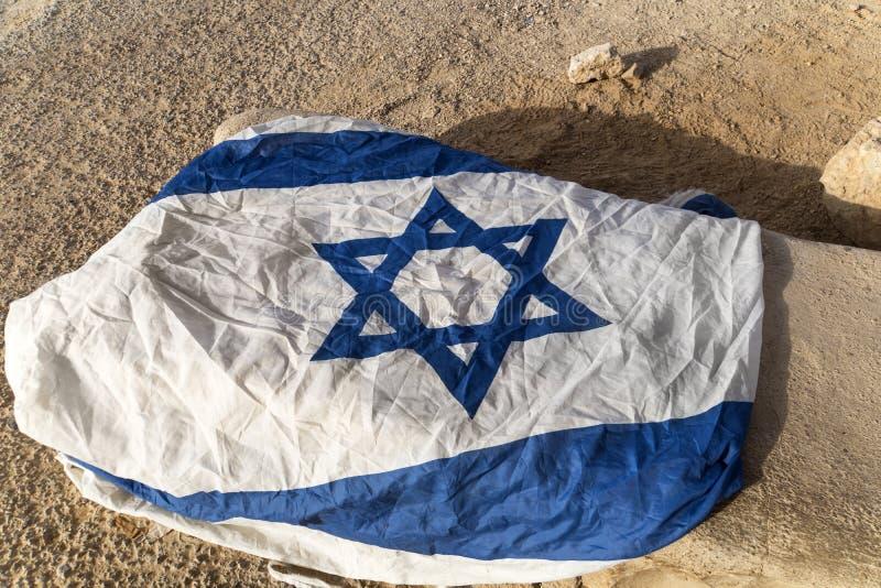 Stäng sig upp av vitt, och den blåa flaggan med Davids stjärna lämnade på jordningen i ointressant ställe Symbol av lovat land Pa arkivbilder