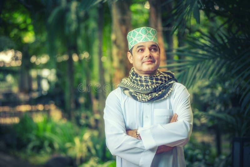 Stäng sig upp av vuxet pakistanskt muslimmananseende och korsa armen arkivfoto