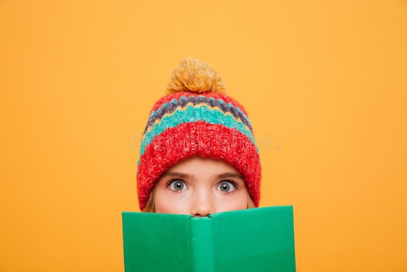 Stäng sig upp bild av den förvånade flickan i tröja och hatt royaltyfri foto