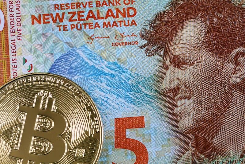 Stäng sig upp bild av en nyazeeländsk räkning för dollar fem med en bitcoin royaltyfri foto