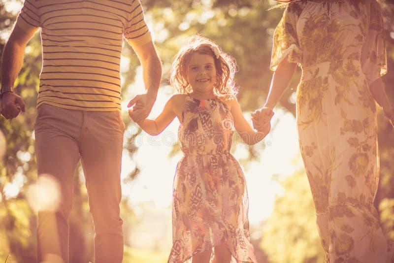 Stäng sig upp bilden av lilla flickan som går med förälderhonaturen royaltyfri fotografi
