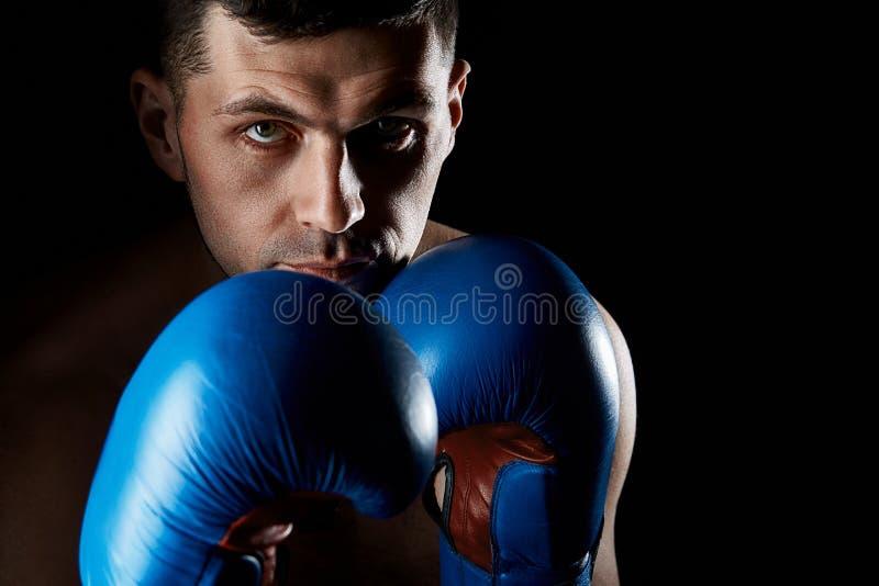 Stäng sig upp bottenlägetangentståenden av en aggressiv muskulös kämpe som visar hans näve som isoleras på mörk bakgrund royaltyfria foton