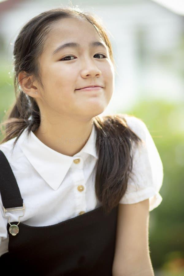 Stäng sig upp den asiatiska tonåringen för huvudskottet som ler framsidan fotografering för bildbyråer