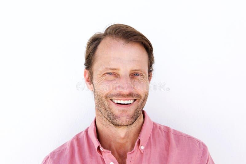 Stäng sig upp den attraktiva mannen som ler mot vit bakgrund arkivbild