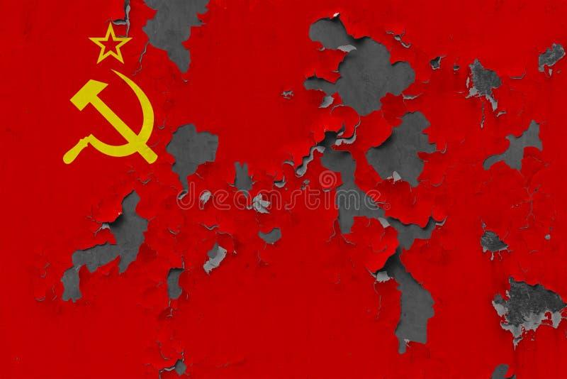Stäng sig upp den grungy, skadade och red ut Sovjetunionen flaggan på väggen som skalar av målarfärg för att se inom yttersida royaltyfri foto