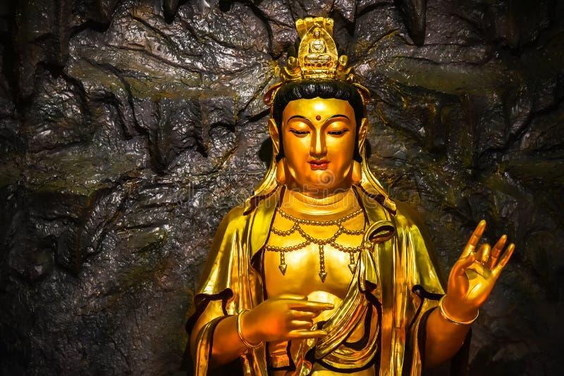 Stäng sig upp den guld- bodhisattvaen Guan Yin som för statyn lokaliseras i grottan på Hangzhou KINA royaltyfri foto