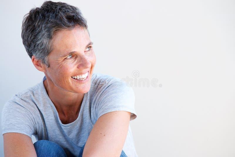 Stäng sig upp den härliga äldre kvinnan som ler mot vit bakgrund arkivfoto