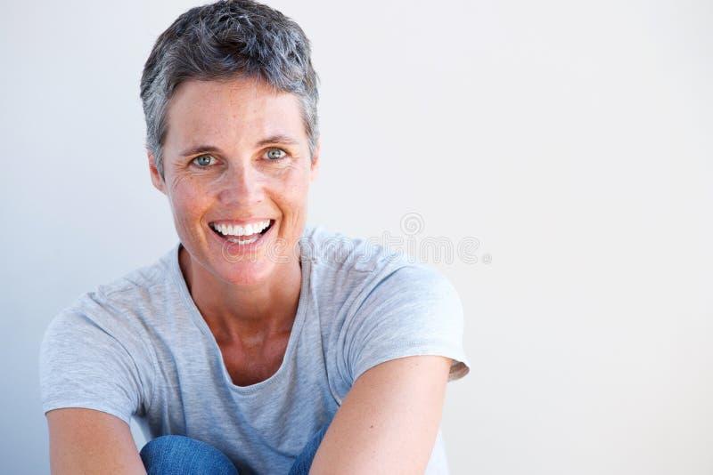 Stäng sig upp den härliga äldre kvinnan som ler mot den vita väggen arkivfoto