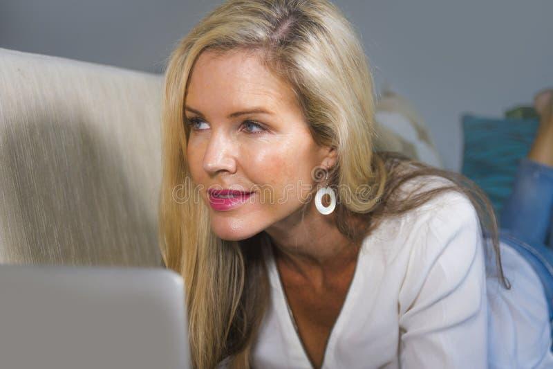 Stäng sig upp den härliga ståenden och den lyckliga blonda kvinna40-tal som hemma kopplas av genom att använda internet på arbeta arkivbild