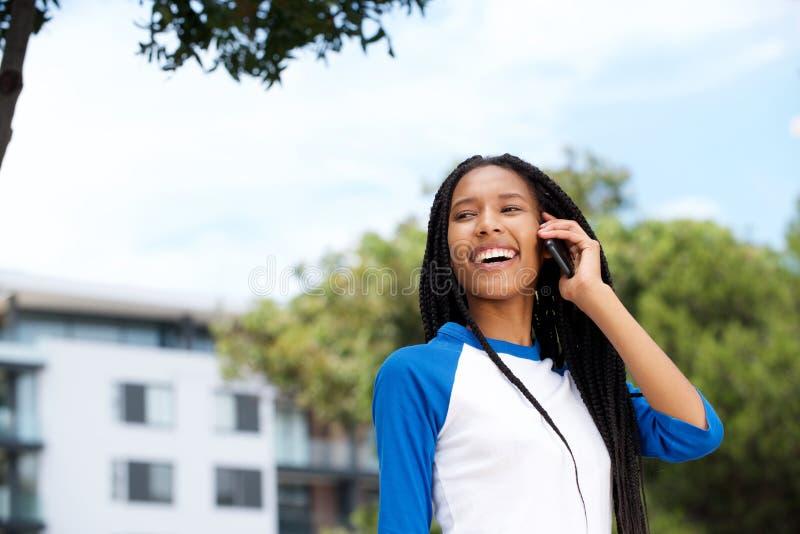Stäng sig upp den härliga svarta flickan som utomhus går och talar på mobiltelefonen arkivfoto