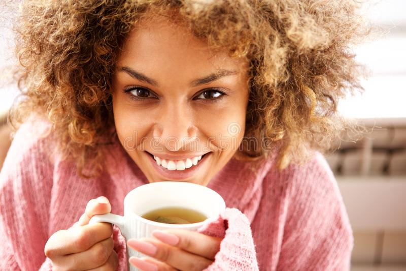 Stäng sig upp den härliga unga afrikansk amerikankvinnan som dricker kopp te arkivbild