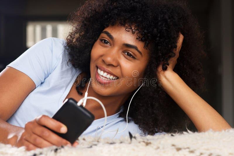 Stäng sig upp den härliga unga afrikanska kvinnan som ligger på golvet som lyssnar till musik med hörlurar och mobiltelefonen arkivfoto