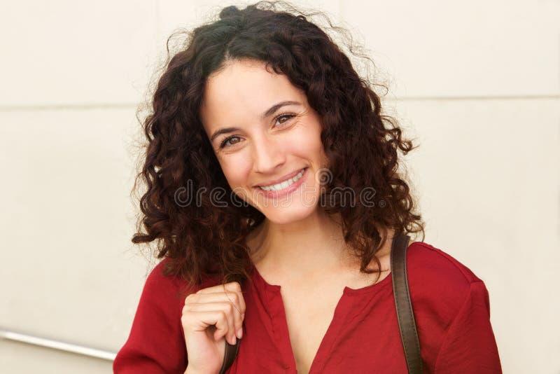 Stäng sig upp den härliga unga kvinnan som ler mot den vita väggen royaltyfri fotografi