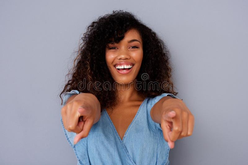 Stäng sig upp den härliga unga svarta kvinnan som ler och pekar fingrar royaltyfri bild
