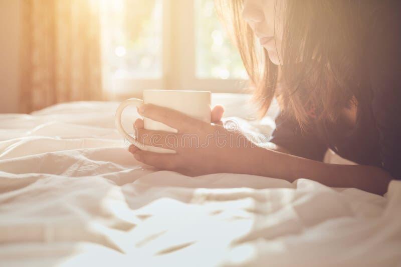 Stäng sig upp den hållande kaffekoppen för kvinnan på sängen i morgontid, fo arkivfoton