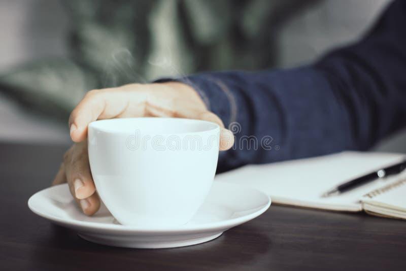 stäng sig upp den hållande koppen kaffe för handen på den funktionsdugliga tabellen royaltyfri foto