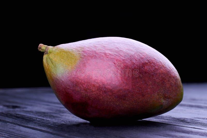 Stäng sig upp den hela nya mango på mörk bakgrund royaltyfri foto
