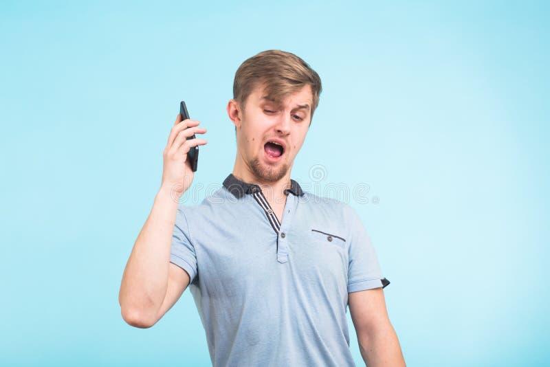 Stäng sig upp den ilskna unga mannen för ståenden, den tokiga studenten för grabben som ropar på telefonen över blå bakgrund Nega royaltyfria foton