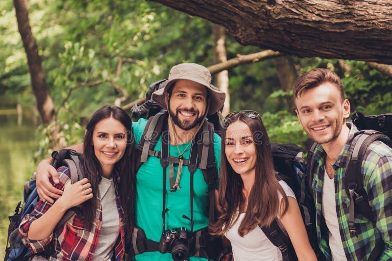 Stäng sig upp den kantjusterade ståenden av fyra gladlynta vänner i det trevliga trät för sommar De är fotvandrare som går och vä royaltyfria bilder