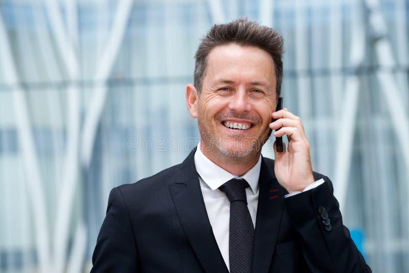 Stäng sig upp den lyckade äldre affärsmannen som talar på mobiltelefonen royaltyfria foton