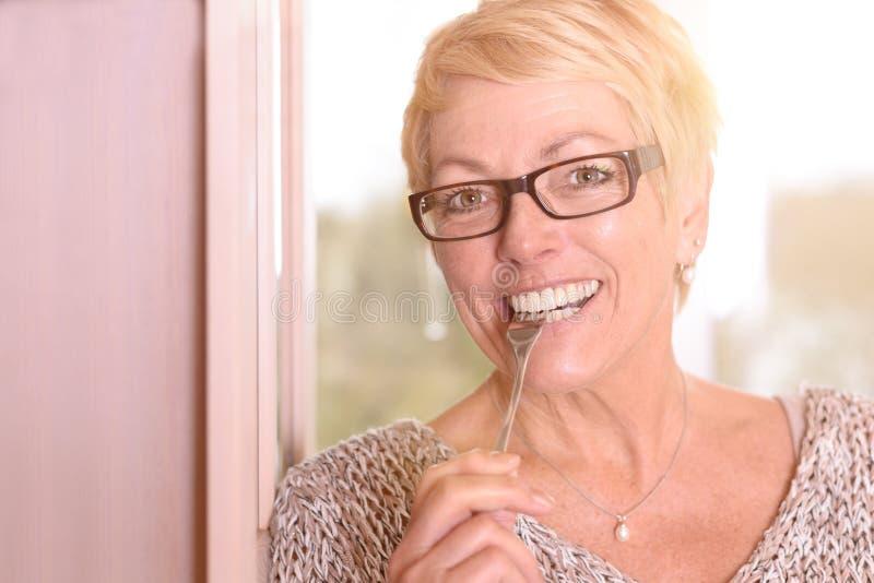 Stäng sig upp den lyckliga blonda kvinnan som biter en gaffel royaltyfri fotografi