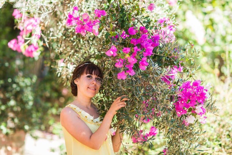 Stäng sig upp den romantiska ståenden av den härliga eleganta kvinnan i blomningträd royaltyfria bilder