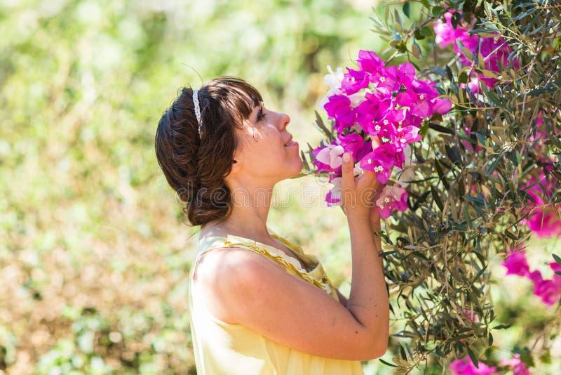 Stäng sig upp den romantiska ståenden av den härliga eleganta kvinnan i blomningträd fotografering för bildbyråer
