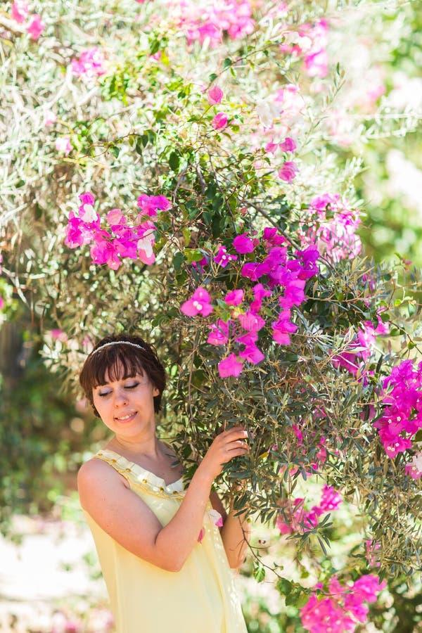 Stäng sig upp den romantiska ståenden av den härliga eleganta kvinnan i blomningträd royaltyfri foto
