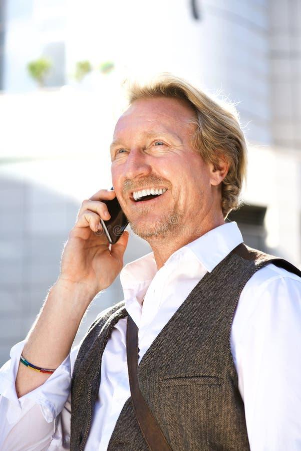 Stäng sig upp den stiliga mannen som talar på mobiltelefonen i stad royaltyfri bild