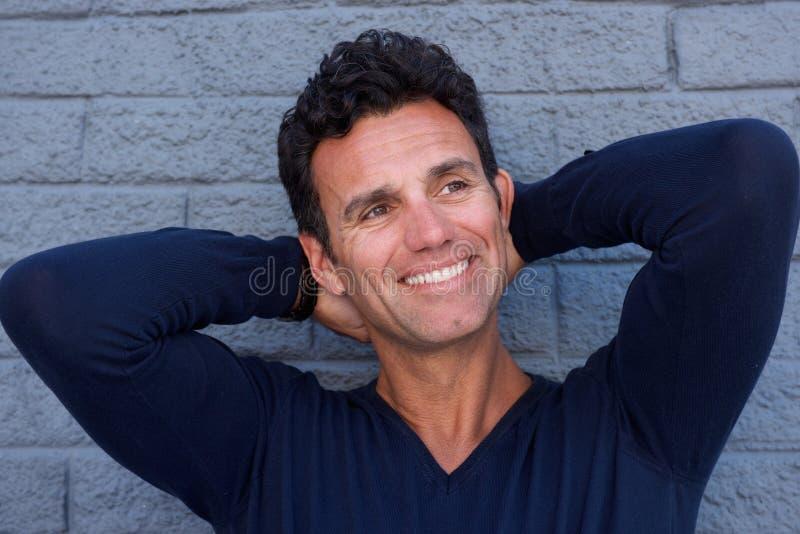 Stäng sig upp den stiliga mogna mannen som ler med händer bak huvudet royaltyfria foton