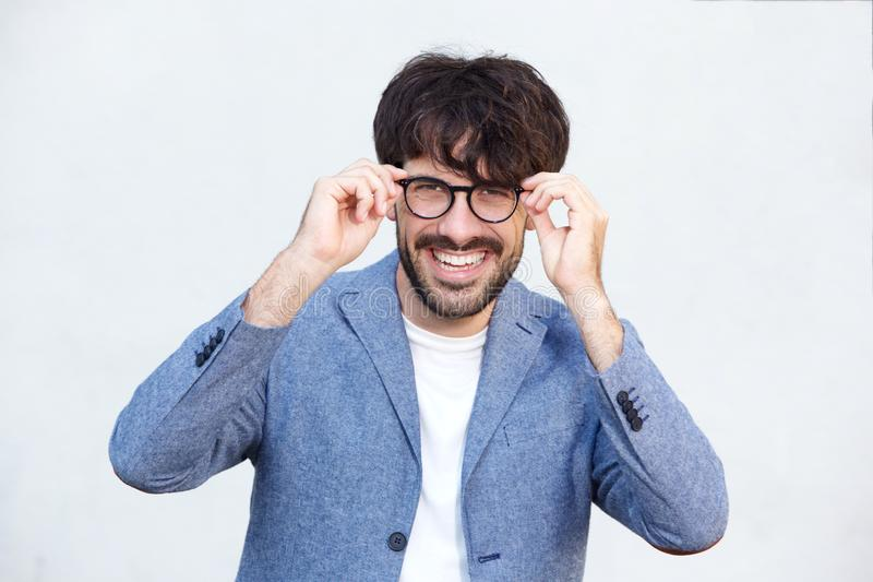 Stäng sig upp den stiliga unga mannen som ler med glasögon mot vit bakgrund royaltyfria bilder